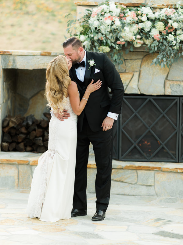 Bride and groom kissing in front of the outdoor fireplace at a murrieta wedding venue