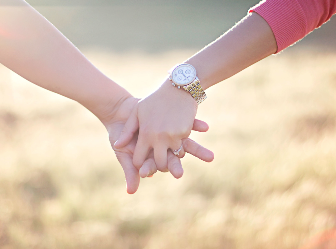 Holding hands in front of a field outdoor.
