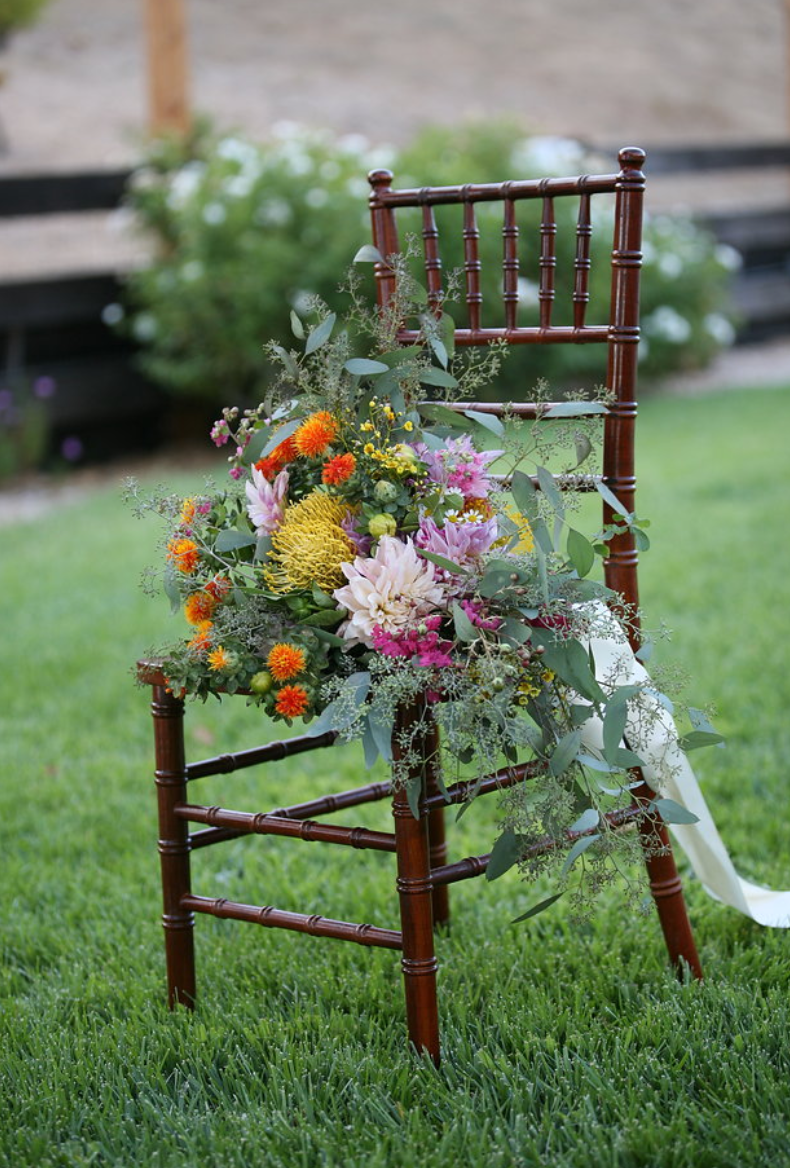 Chivalry chair on the grass with a bridal bouquet on the seat.  Beautiful outdoor backdrop.